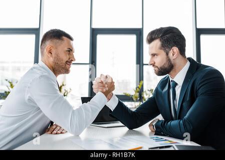 Stattliche Geschäftsleute konkurrierenden Armdrücken in modernen Büro - Stockfoto