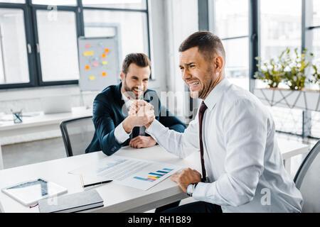 Geschäftsleute in formale Abnutzung konkurrierenden Armdrücken in modernen Büro - Stockfoto