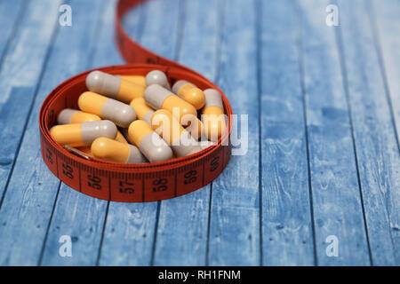 Diätpillen, Gewichtsverlust beseitigen. Medikation in Kapseln und Maßband auf hölzernen Tisch - Stockfoto