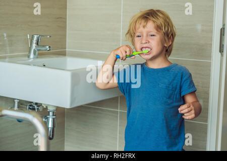 Kleine blonde Junge lernen seine Zähne putzen in der heimischen Badewanne. Kinder lernen, gesund zu bleiben. Health Care Konzept - Stockfoto