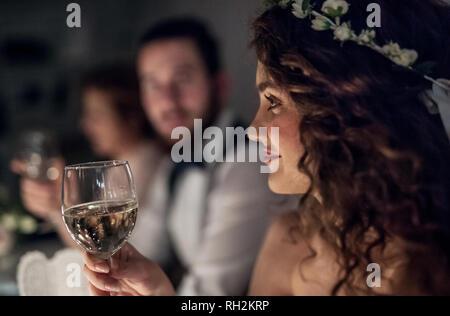 Eine Nahaufnahme einer jungen Braut an einem Tisch auf einer Hochzeit sitzend, mit einem Glas Weißwein. - Stockfoto