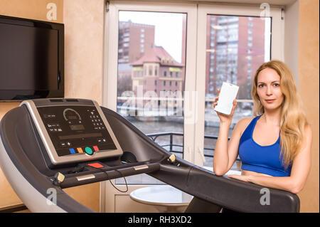 Junge schöne erwachsenen Mädchen mit Perfect Slim Abbildung in der Turnhalle auf Fitness mit Telefon in der Hand - Stockfoto