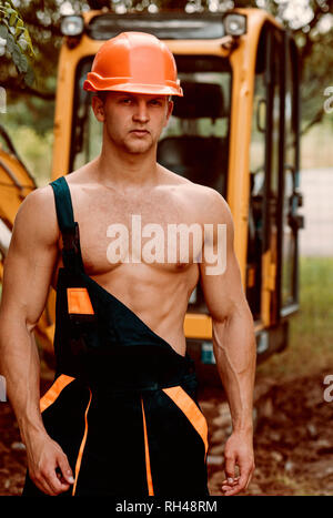Operator Konzept. Baggerführers auf der Baustelle. Muskulöse operator in Uniform. Maschinenbediener mit Digger. - Stockfoto