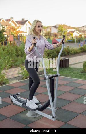 Passende Frau mit elliptischen Maschine auf der Terrasse - Stockfoto