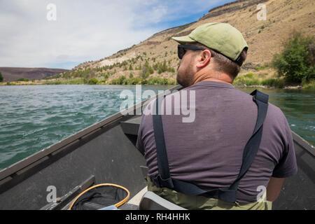 Fischer sitzen in einem Drift boot Fliegen beim Schwimmen den Fluss auf die nächsten Fischerei der Zugang auf der unteren Deschutes River in der Nähe von warmen Quellen Oregon zu erhalten - Stockfoto