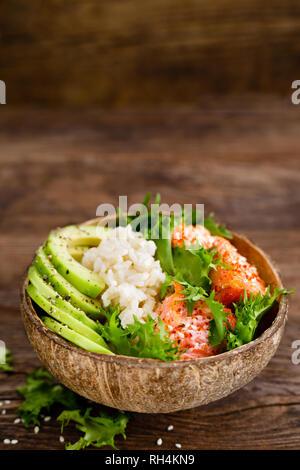 Hawaiian poke Kokosnuss Schale mit gegrillter Lachs Fisch, Reis und Avocado. Gesunde Ernährung - Stockfoto