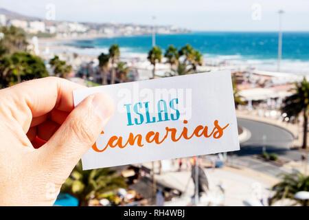Nahaufnahme der Hand eines kaukasischen Mann hält ein Schild mit dem Text Islas Canarias Kanarische Inseln auf Spanisch geschrieben, bei Playa del Ingles, in Ma - Stockfoto