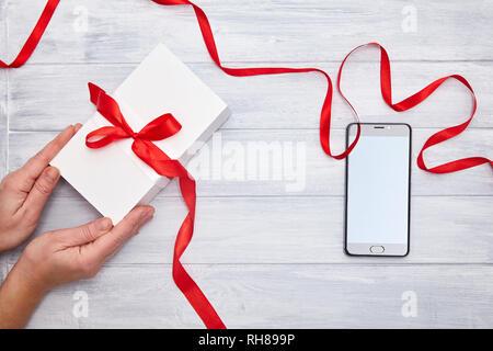 Weißes Gift Box in Händen mit roter Schleife und Smartphone auf einem woodem Hintergrund. Geburtstag, Weihnachten, Geschenk Valentinstag Konzept - Stockfoto