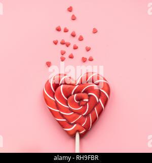 Valentine's Karte. Lutscher Süßigkeiten wie Herzen auf rosa Hintergrund. Lustiges Konzept. - Stockfoto