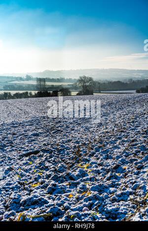 Am frühen Morgen winter Aussicht, an einem sonnigen Tag über einen schneebedeckten gepflügten Feldes zu entfernten Misty Hills in den Cotswolds, Gloucestershire, VEREINIGTES KÖNIGREICH - Stockfoto