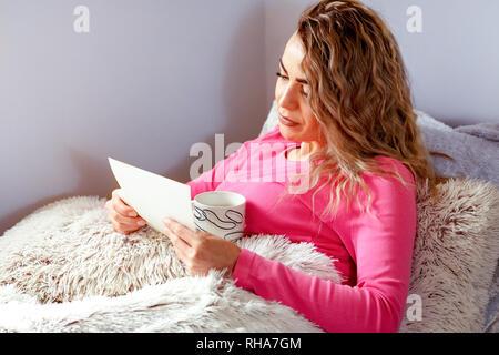 Fröhliche junge Frau, die am alten Familienfotos suchen - Stockfoto