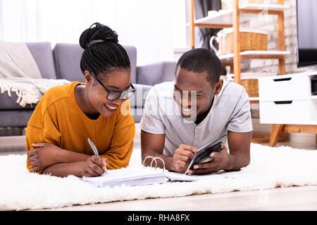 Junge afrikanische Paar Liegen auf dem Teppich Rechnung mit Taschenrechner - Stockfoto
