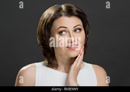 Wunderschöne reife Brunette mit grünen Augen. Das Bild in einem Studio auf einem grauen Hintergrund genommen wurde. - Stockfoto