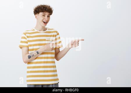 Freundlich - Suchen awesome junger Kerl mit Curly Frisur und Tattoos nach rechts mit Zeigefinger und Blick auf die Kamera als breit grinsend und - Stockfoto