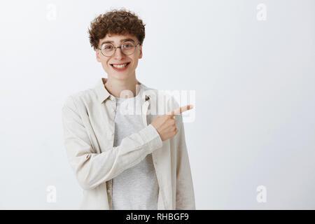 Curly-haired Kerl zeigt Weg zu Favorit cafe heraus hängen mit Mitschüler rechts und lächelt freundlich auf Kamera in trendigen Shirts posing und - Stockfoto
