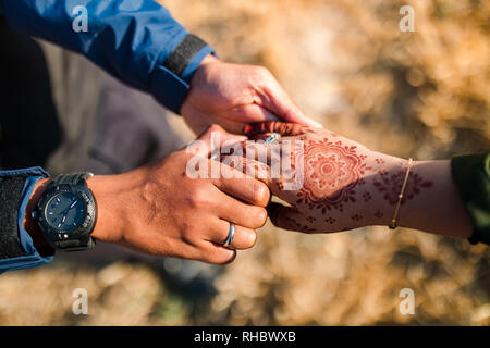 Junge und glückliche Paare halten sich an den Händen. Mann oder Junge und Mädchen hielten ihre Hände. Die Hand des Mädchens hat Henna. Asiatische paar Liebe. - Stockfoto