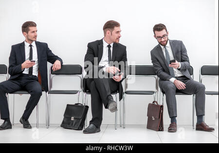 Mitarbeiter mit Smartphones im Büro Flur sitzen - Stockfoto