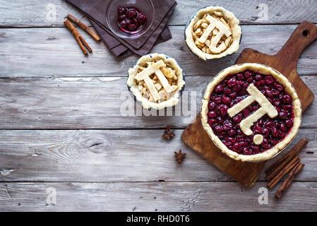 Pi-Tag Cherry und Apple Pies, hausgemachte, traditionelle verschiedene Torten mit Pi-Zeichen für 14. März Urlaub, auf rustikalen Holzmöbeln Hintergrund, Ansicht von oben, Co - Stockfoto
