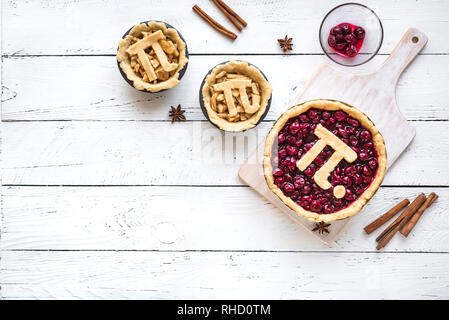 Pi-Tag Cherry und Apple Pies, hausgemachte, traditionelle verschiedene Torten mit Pi-Zeichen für 14. März Urlaub, auf weißem Hintergrund Holz, Ansicht von oben, cop - Stockfoto
