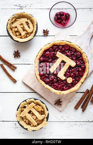 Pi-Tag Cherry und Apple Pies, hausgemachte, traditionelle verschiedene Torten mit Pi-Zeichen für 14. März Urlaub, auf weißem Hintergrund Holz, Ansicht von oben. - Stockfoto