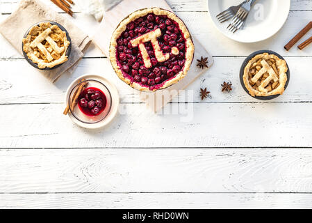 Pi-Tag Cherry und Apple Pies - hausgemachte, traditionelle verschiedene Torten mit Pi-Zeichen für 14. März Urlaub, auf weißem Hintergrund Holz, Ansicht von oben, kopieren Raum - Stockfoto