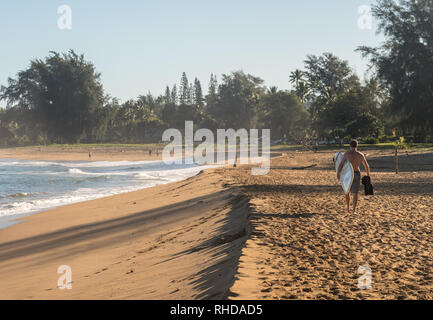 Mann, der Surfboard zu Ocean auf sandigen Hanalei Beach - Stockfoto