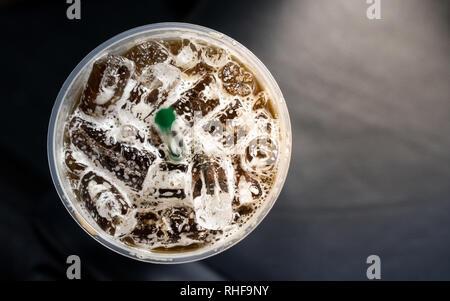 Blick von oben auf Eis Kaffee in einem plasstic Glas mit Strohhalm - Stockfoto