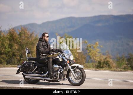 Seitenansicht des bärtigen langhaarigen Motorradfahrer mit Sonnenbrille und schwarzem Leder kleidung Reiten cruiser Motorrad auf schmalen asphaltierten Weg an einem sonnigen Tag - Stockfoto