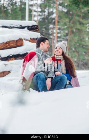 Lächelnden jungen Paar mit cups im Snow park sitzen. Trinken Sie heiße Getränke, Spaß zu haben. - Stockfoto