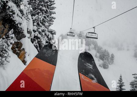 Ski Sessellift bringt Skifahrer und Snowboarder auf den Berg bei starkem Schneefall auf einem nebligen Wintertag in Courchevel, Frankreich.