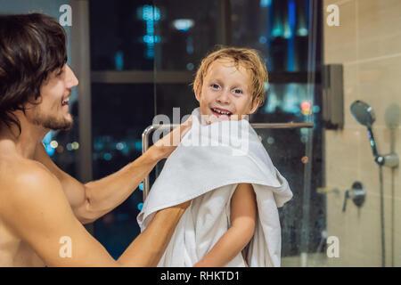 Vati Wischtücher seinen Sohn mit einem Handtuch nach einem abendlichen Dusche vor dem Hintergrund der ein Fenster mit einem Panoramablick auf die Stadt zu schlafen - Stockfoto