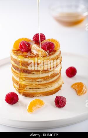 Amerikanische Süße hausgemachte Stapel Pfannkuchen oder Krapfen mit Himbeere Früchte und Honig, leckeres Dessert für Frühstück, auf weißem Hintergrund. Selektive - Stockfoto