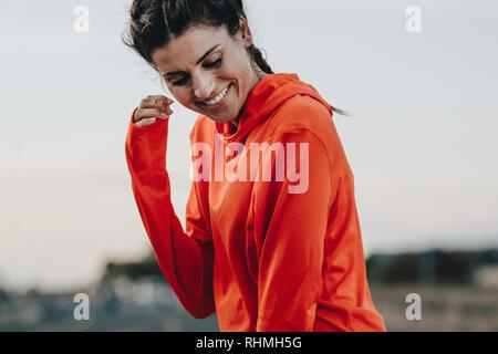 Lächelnd Sportlerin im Trainingsanzug stand im Freien. Fitness Frau unter brechen auf nach einem Morgen laufen. - Stockfoto