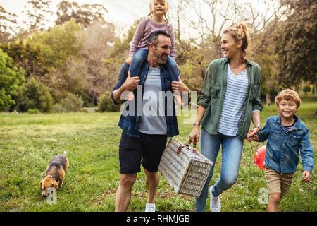 Glückliche Familie mit Hund auf dem Weg zur Laube im Garten. Mann, der seine Tochter auf der Schulter mit Frau mit Sohn und mit einer Hand - Stockfoto