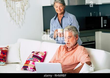 Ältere Erwachsene kaukasischen Paar zu Hause mit Laptop moderne Computer mit Internetzugang und eine gute Zeit zusammen in der Ehe Lifestyle - Küche im Hinterg - Stockfoto