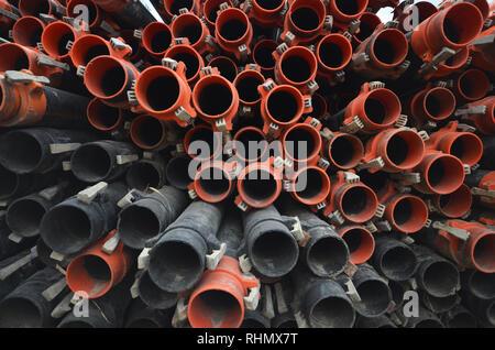 Hintergrund der Kunststoff Gummi Leitungen. Große Gruppe und Stapel von orange und schwarz Sanitär Kunststoff Gummi Leitungen. Industrielle Bewässerung aus Kunststoff Rohre voll - Stockfoto
