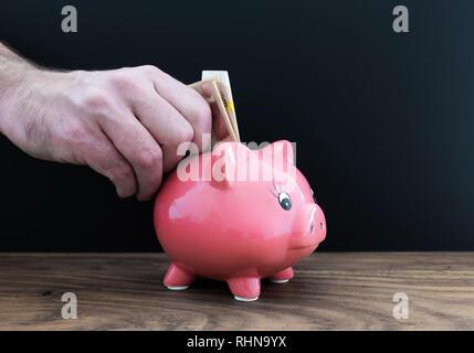 Hand Geld in piggy Bank - Stockfoto