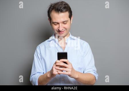 Studio Portrait des jungen Mannes SMS auf Handy - Stockfoto