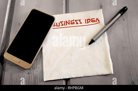 Business Startup Idea Note auf dem Papier Serviette mit Handy und Stift, auf einer hölzernen Oberfläche - Stockfoto