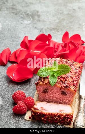 Rosa Himbeere Brot Kuchen mit Rosenblätter auf Graue Tabelle - Stockfoto
