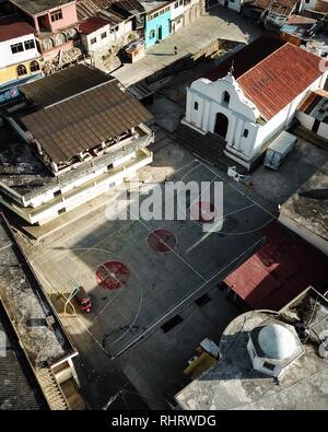 Luftaufnahme von einem Basketballplatz in Santa Cruz, Atitlan See, Guatemala mit einem Tuc Tuc taxi und eine Dame zu Fuß Stockfoto