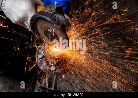 Eine Nahaufnahme von einem Automechaniker mit einem Metall Grinder ein Auto silent Block in einen Schraubstock in einer Werkstatt zu schneiden, helle Blitze fliegen in verschiedenen dire - Stockfoto