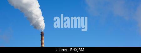 Weißer Rauch kommt aus Rohren gegen den blauen Himmel - Stockfoto