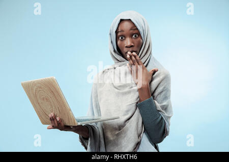 Portrait von weiblichen Studenten Arbeiten am Laptop. Die schöne junge schwarze afrikanische muslimische Mädchen mit grauen Hijab im Blue Studio. Sie stehen mit überrascht Emotion auf ihrem Gesicht. - Stockfoto