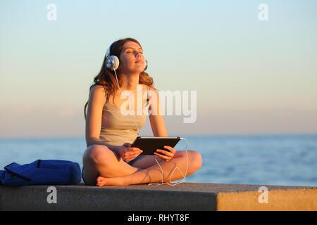 Voller Körper Portrait von Student entspannten Musikhören von Tablet sitzen auf einer Bank am Strand - Stockfoto