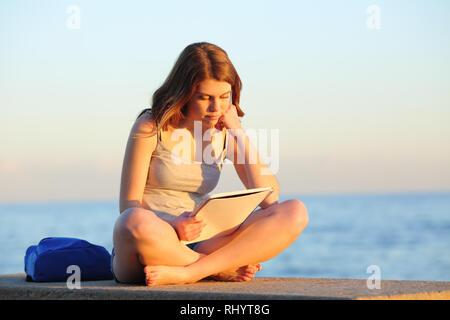 Voller Körper Porträt eines fleißigen Studenten studieren Lesen von Notizen, die auf einer Bank sitzen am Strand - Stockfoto