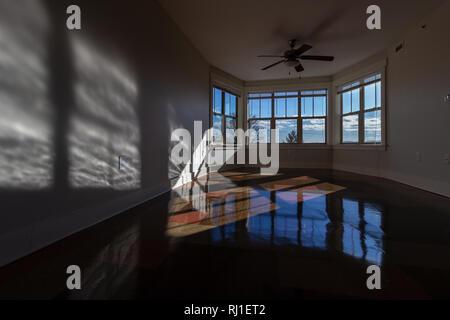 Am späten Nachmittag Sonne durch arge bay Windows erstellen Sie schöne Schatten und Spiegelungen auf glänzenden Vinyl Bodenbelag. - Stockfoto