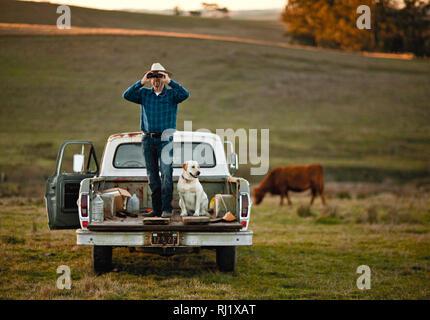 Ein mann und sein hund blick durch sein fernglas für vögel über
