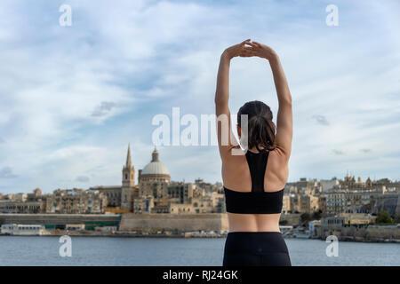 Zurück Blick auf eine Frau, der eine Arm stretch Warm up Übung. Valletta Malta Hintergrund. - Stockfoto
