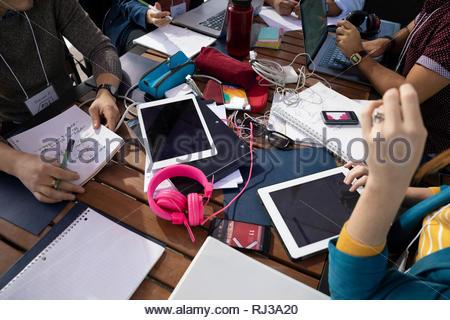 Tausendjährige Unternehmer arbeiten, mithilfe von digitalen Tabletten und Laptops in Tabelle - Stockfoto
